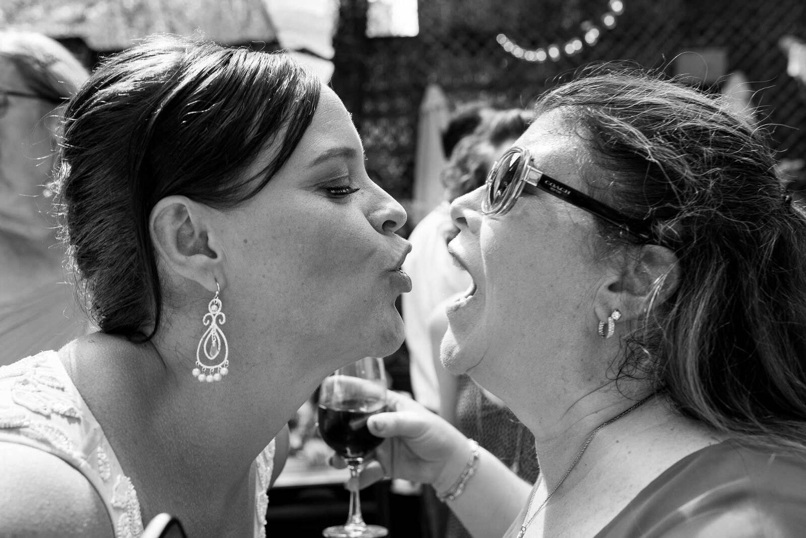 Bride and friend about to kiss at New York City wedding reception under Brooklyn bridge