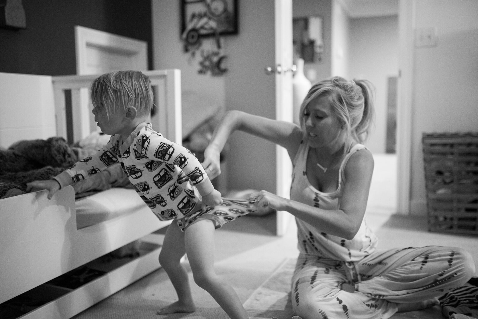 Mom trying to change son's diaper before getting dressed for his first day of school