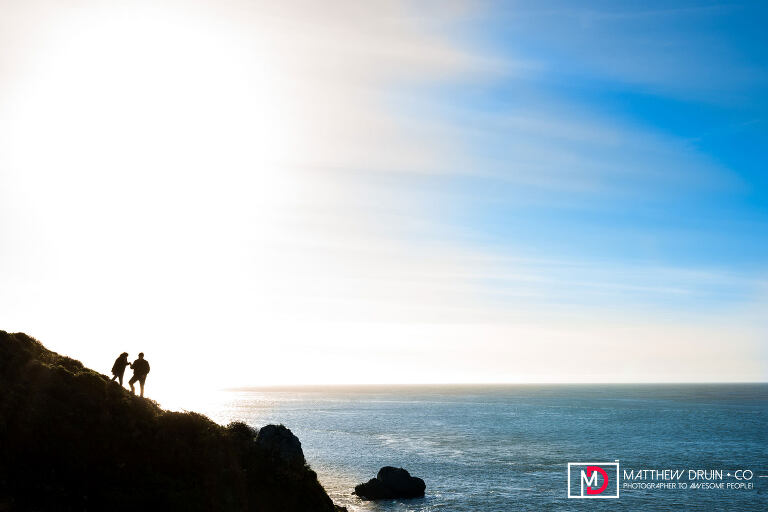 Silhouette of couple climbing cliffs by ocean during their San Francisco Golden Gate Bridge engagement