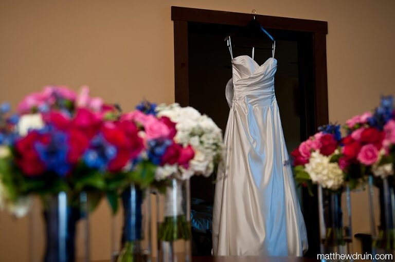Lake Lanier Islands Wedding dress hanging up with pink, red, and purple flower bouquets
