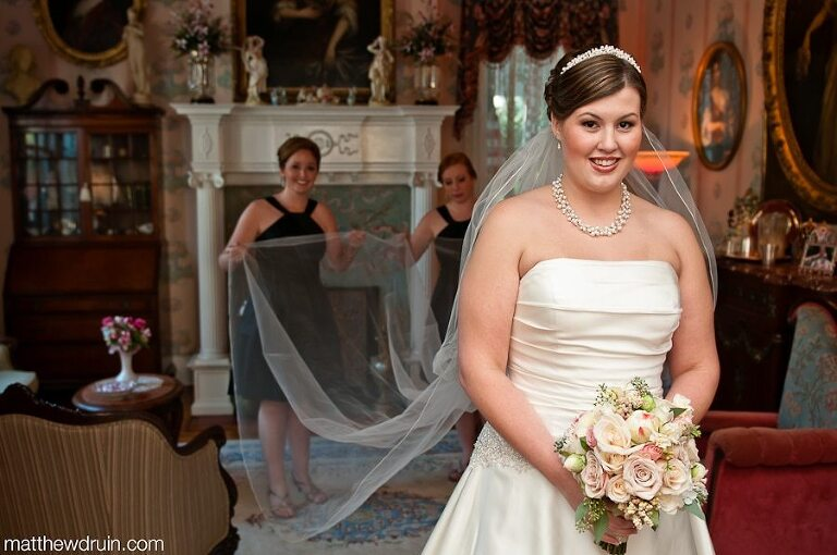 Bride holding bouquet while bridesmaids pulling bride's long vail out before Atlanta wedding