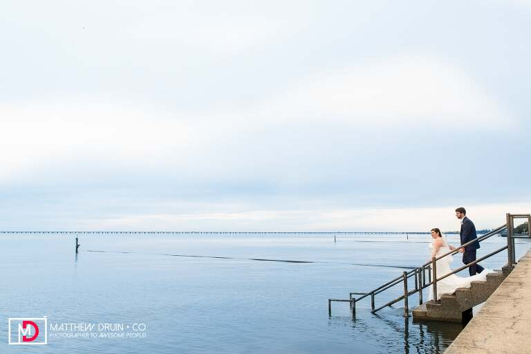 Bride and groom walking down stairs into ocean at New Orleans wedding