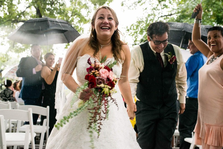 Bride and groom leaving in the rain at wedding ceremony at destination rainy day wedding in Orlando wedding