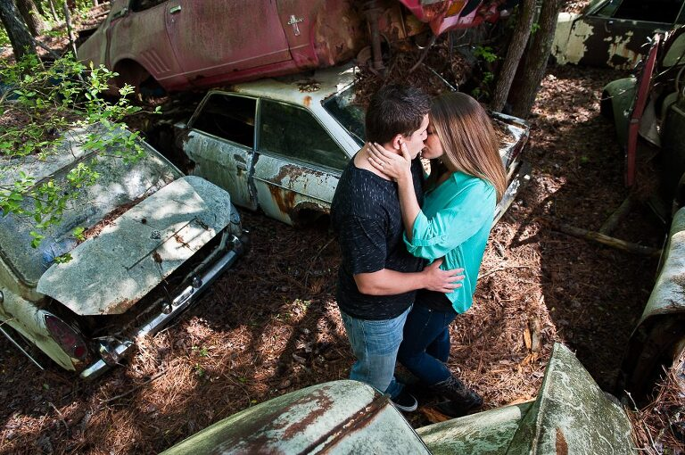 Portrait of engaged couple kissing in junkyard Atlanta, Georgia