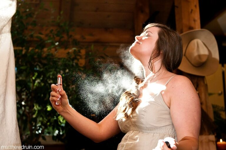Bride spraying perfume in sunlight at Neverland Farms wedding from Atlanta Wedding Photographers Matthew Druin + Co.