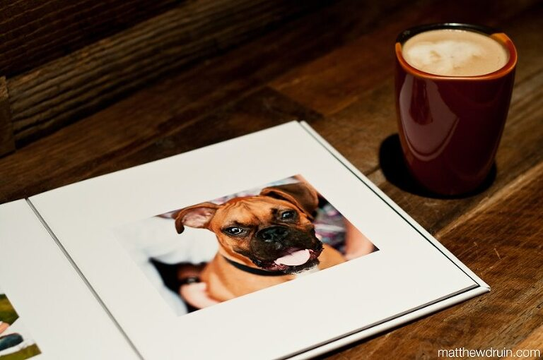 Atlanta wedding guest books laying flat on wood table showing engagement photo of dog with a cup of coffee
