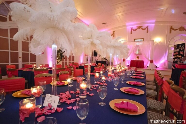 Pink & Blue wedding reception with gold plates and large white feather centerpieces at Atlanta wedding photos