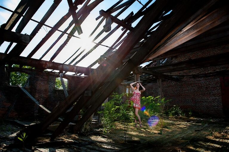 Redhead girl in red flower dress standing in green brush with sun flare for fashion portraits in an abandoned old mill in Augusta Georgia