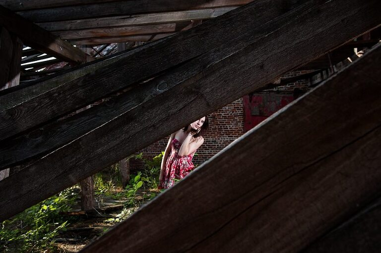 Redhead girl in red flower dress standing in broken building looking through wood at camera for fashion portraits in an abandoned old mill in Augusta Georgia