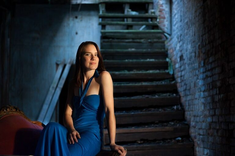 Redhead girl in blue dress sitting on red chair in blue basement with stairs in the background for fashion portraits in an abandoned old mill in Augusta Georgia