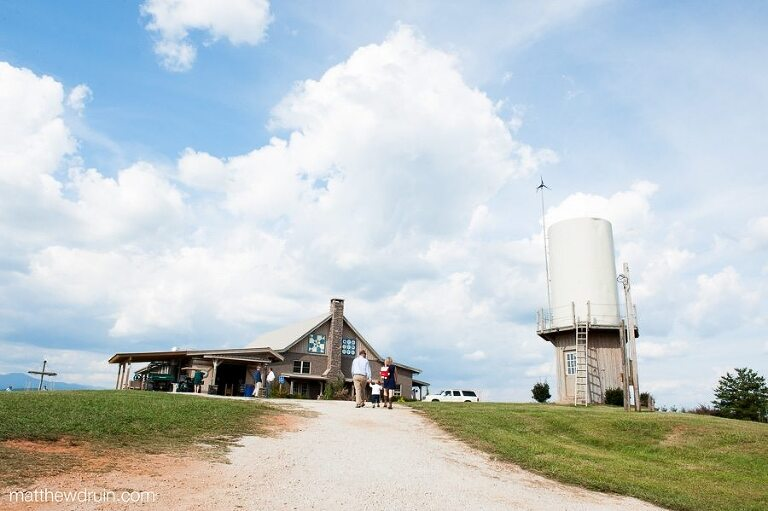 Guests walking up drive with barn and water tower in background at Chattooga Belle Farm South Carolina wedding