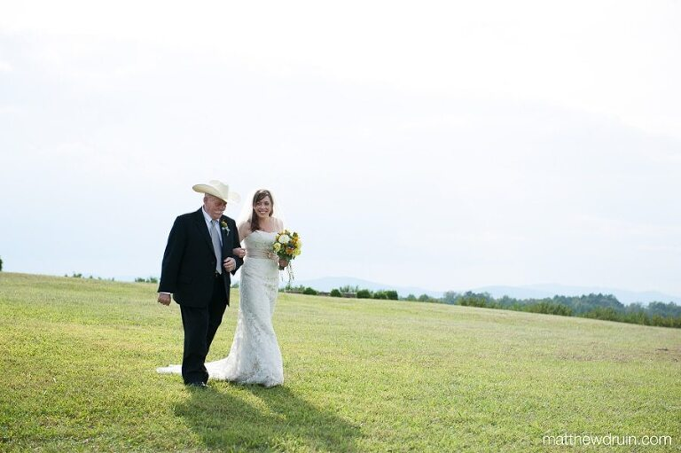 Father And Bride Walking To Wedding Ceremony In Wine Vineyard With Blue Ridge Mountains Background