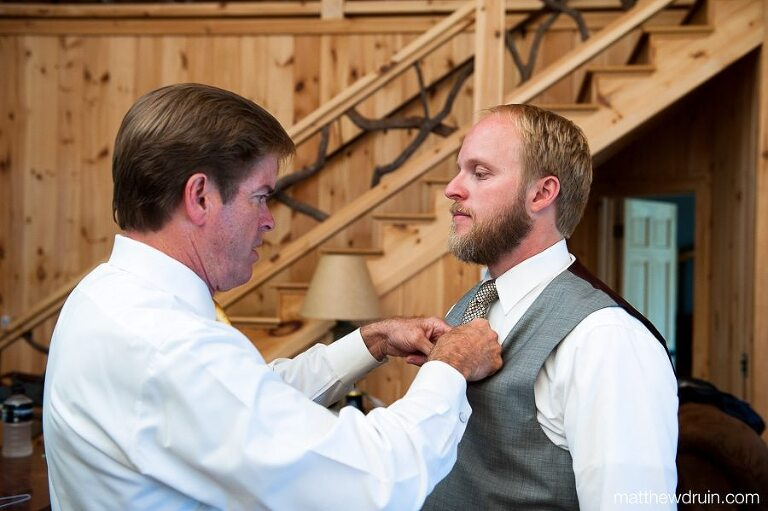 Father helping groom with tie in log cabin at Chattooga Belle Farm South Carolina wedding