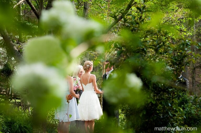 Bride and groom holding hands at ceremony shot through trees at Neverland Farms