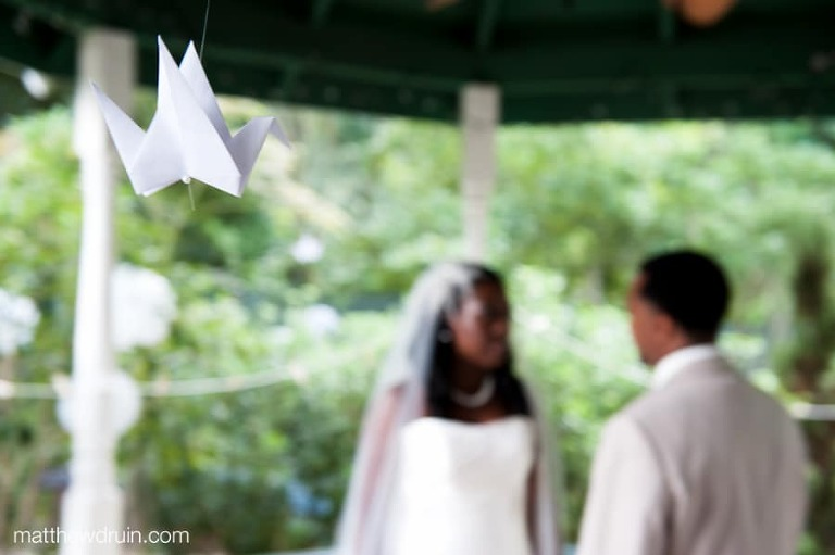 Paper origami bird hanging with bride and groom out of focus during first look at South Carolina wedding