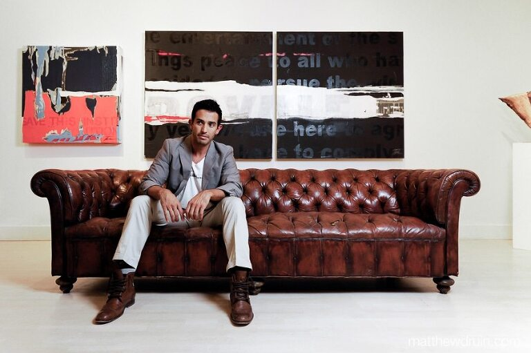 Atlanta artist Luis Toache sitting on leather couch in art studio for Jezebel Magazine
