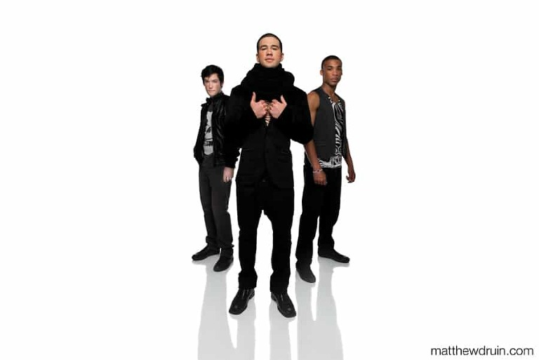 Atlanta music band wearing all black standing on white seamless with shadows in studio for press kit