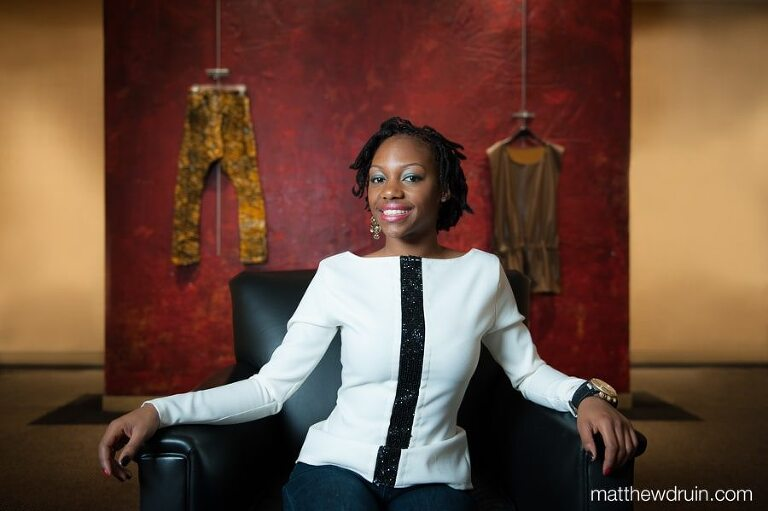 Atlanta fashion designer, Valencia White, from Art Institute of Atlanta for Jezebel Magazine sitting in leather chair with red and yellow wall