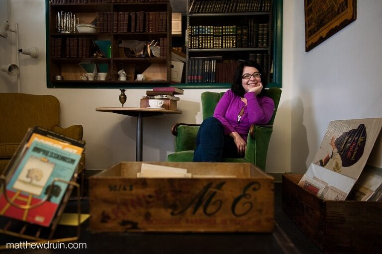 Meghan Stoneburner Atlanta SEO expert wearing purple sweater sitting on green chair Atlanta Vintage Books