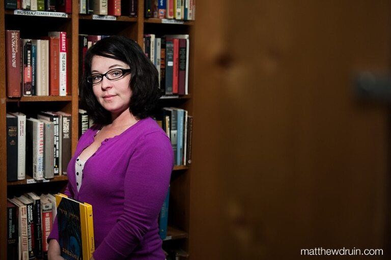 Meghan Stoneburner Atlanta SEO expert wearing purple sweater holding yellow book ini bookshelves Atlanta Vintage Books