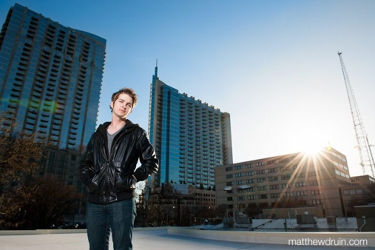 MusicAtlanta musician Jordan Green standing on rooftop with leather jacket between buildings with blue sky at sunset