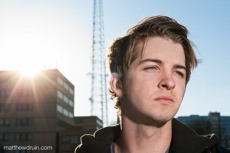 Atlanta musician Jordan Green on rooftop in downtown with sunburst sunset over building with blue sky
