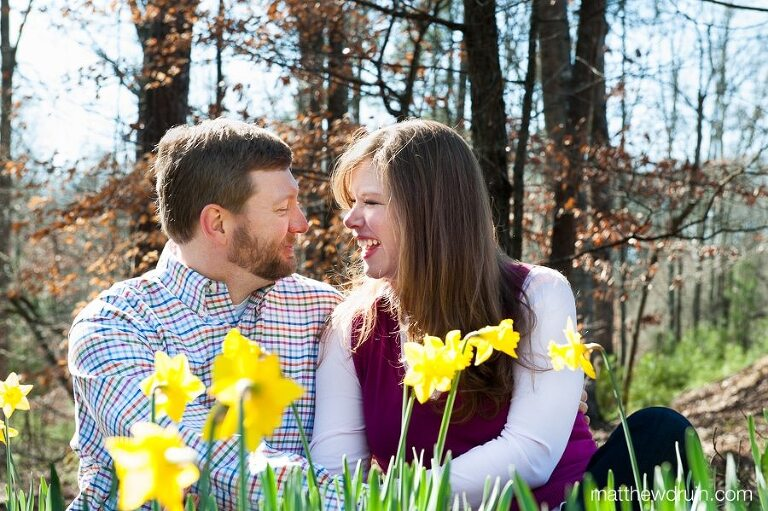Engaged couple laughing while sitting in yellow Lily flowers at Gibbs Gardens in Atlanta, GA