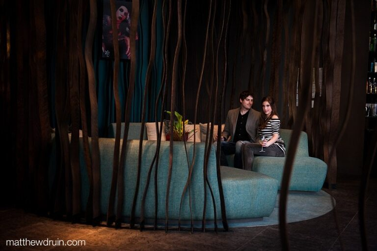 Engaged couple with drinks sitting on teal couch with large wood vines at Atlanta W hotel engagement