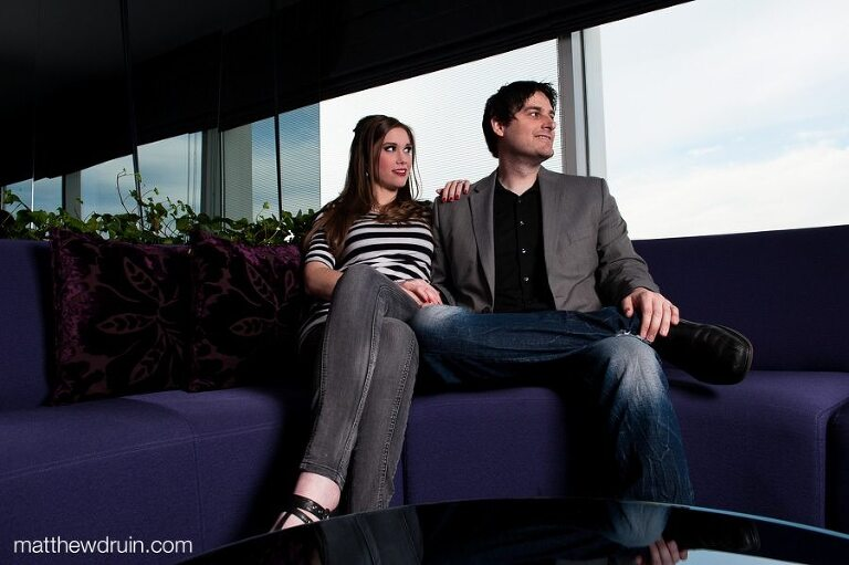 Engaged couple sitting on purple couch looking out window at Atlanta W hotel engagement