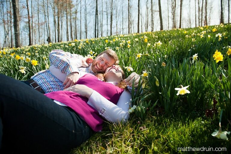 Engaged couple laying and laughing in yellow Lily flowers and green grass at Gibbs Gardens in Atlanta, GA