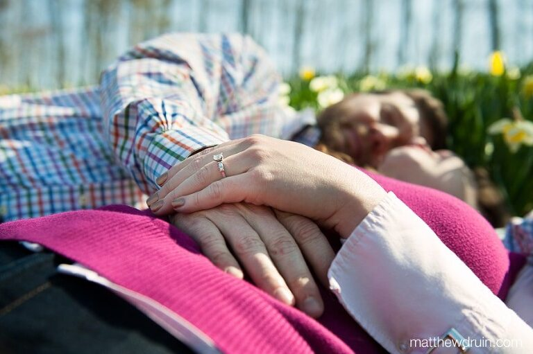 Engaged couple laying in Lily flowers at Gibbs Gardens engagement