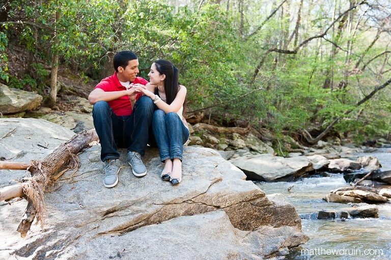 Engaged couple sitting by river at Soap Creek in Atlanta, GA