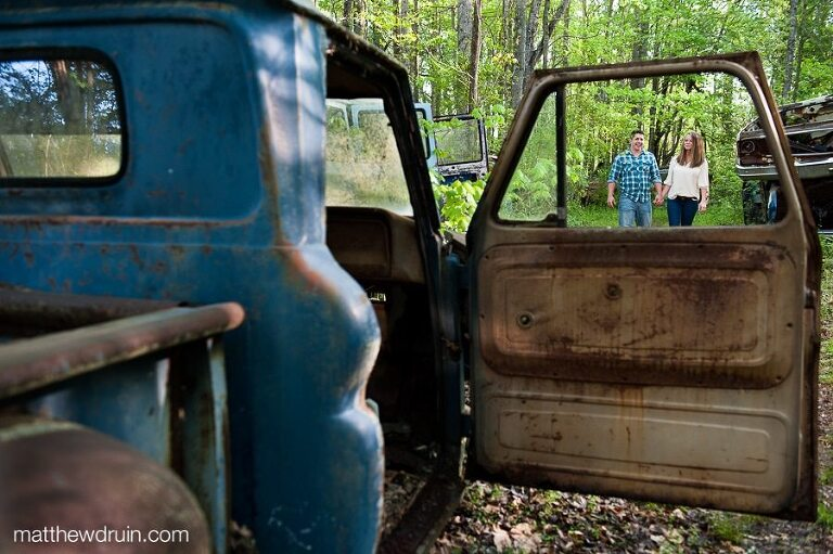 Engaged couple walking and holding hands shot through old blue truck window at Junkyard engagement session
