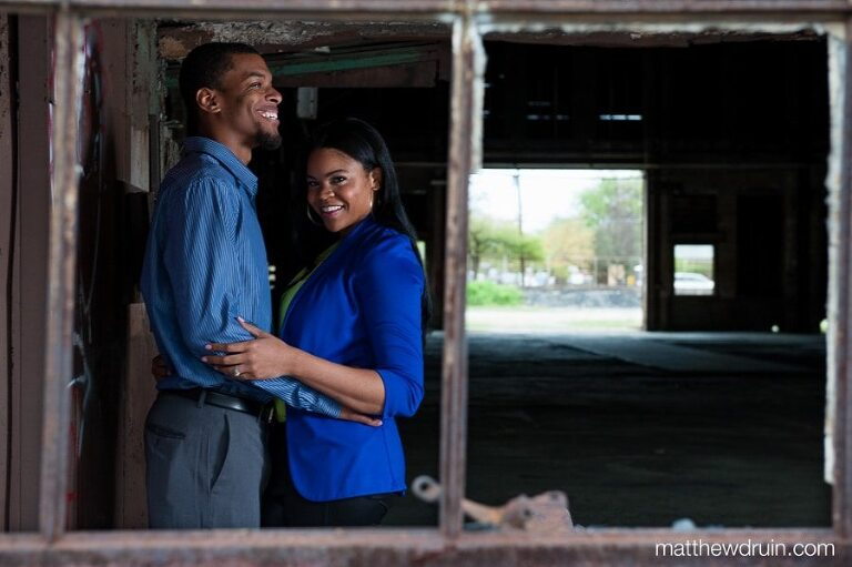 Engaged couple wearing blue standing in old warehouse shot through broken out window at abandoned building engagement