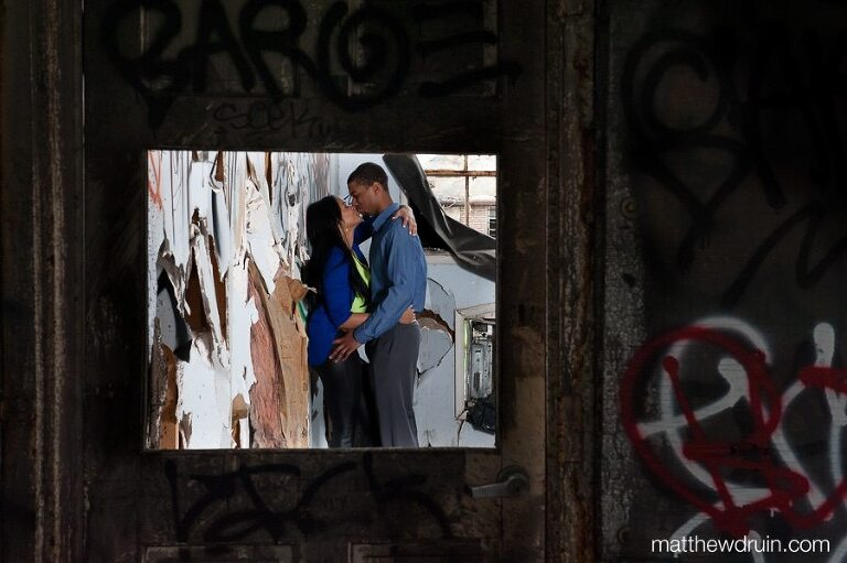 Engaged couple leaning against paint peeling wall with graffiti shot through broken window at abandoned building engagement