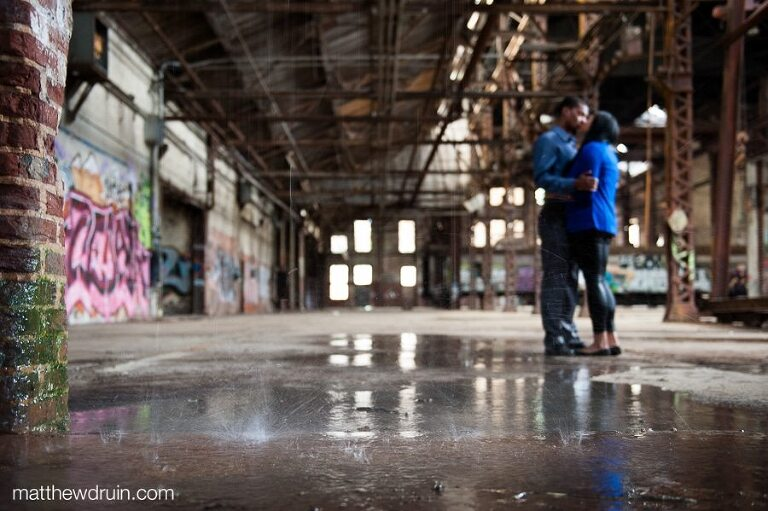 Out of focus engaged couple kissing in graffiti filled warehouse with rain pouring down at abandoned building engagement