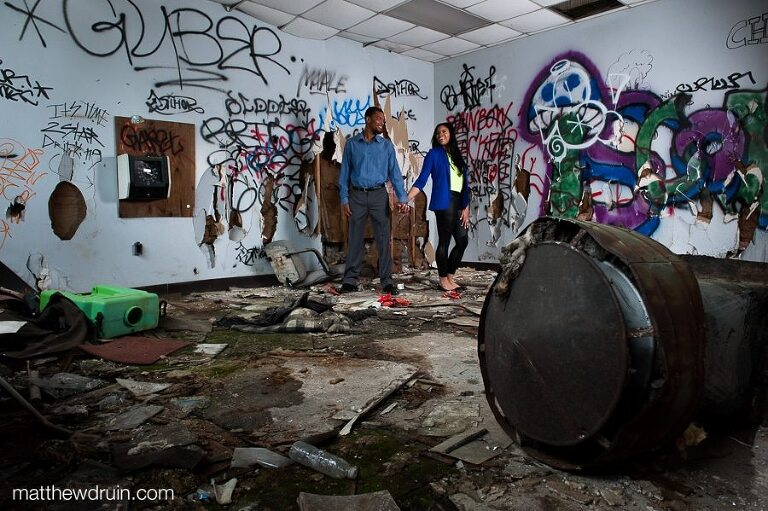 Engaged couple wearing blue standing in graffiti filled room with junk at abandoned building engagement