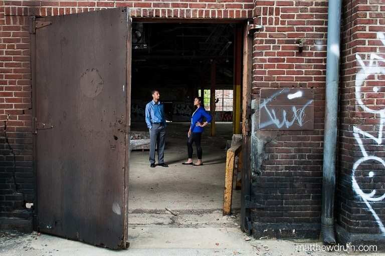 Engaged couple wearing blue standing in old brick building at abandoned building engagement