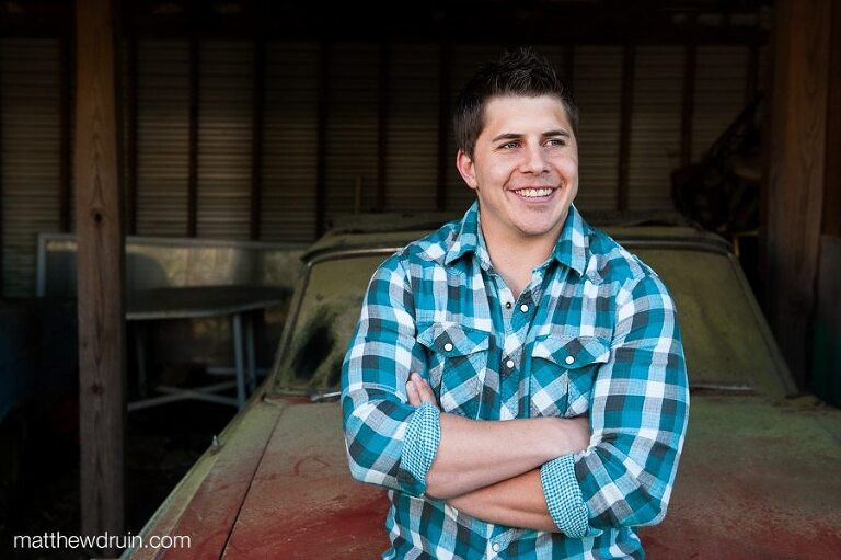Portrait of guy wearing blue plaid shirt sitting on old dusty red car at Junkyard engagement session