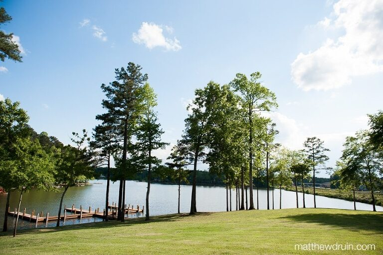 Landscape shot of Crooked Creek Marina with lake and dock with blue sky at Georgia lakeside wedding