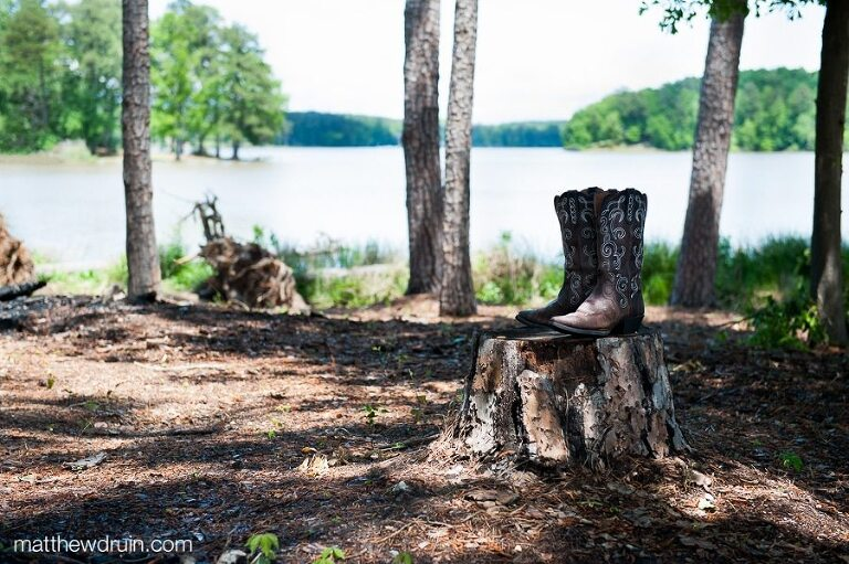 Bride's wedding cowboy boots sitting on wood tree stump for Georgia lakeside wedding