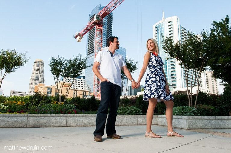 Engaged couple standing by construction with skyscrapers at Midtown Atlanta engagement