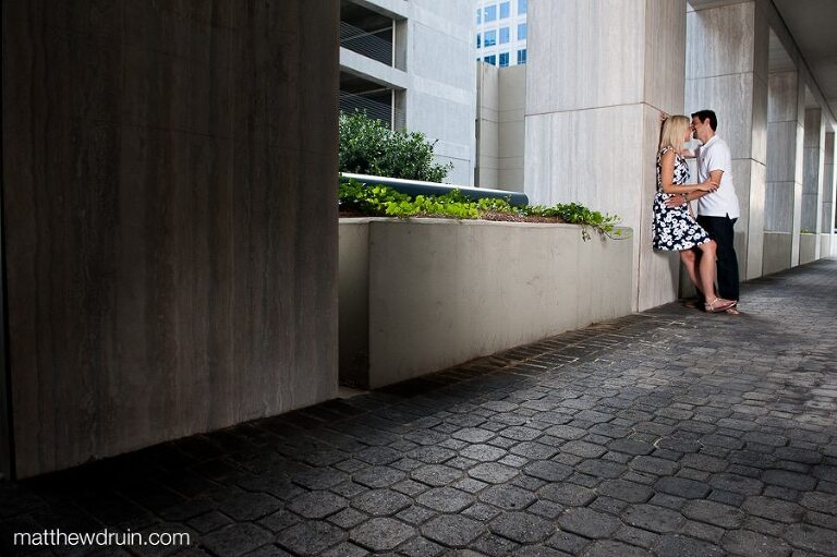 Engaged couple leaning against wall kissing at Midtown Atlanta engagement