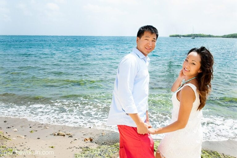Engaged couple holding hands and looking at camera on beach with ocean St. Croix Virgin Islands engagement session