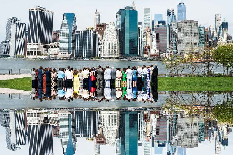 New York City wedding ceremony under Brooklyn Bridge with reflection of Manhattan Skyline