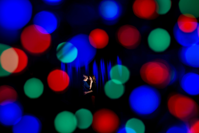 Gay couple holding each other on stage at The Masquerade with blue backdrop and colorful bokeh balls in Atlanta