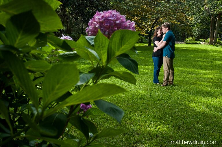 Engaged couple hugging in green grass with purple flowers at savannah engagement session