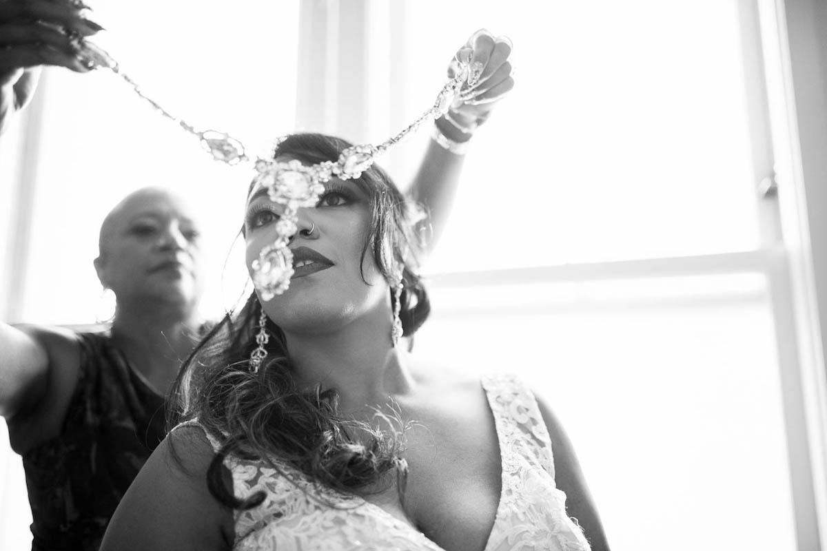 Mom putting jewel necklace on bride at San Francisco wedding at Marines Memorial Club Hotel