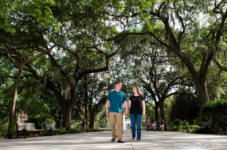 Engaged couple walking in Forsyth Park at savannah engagement session
