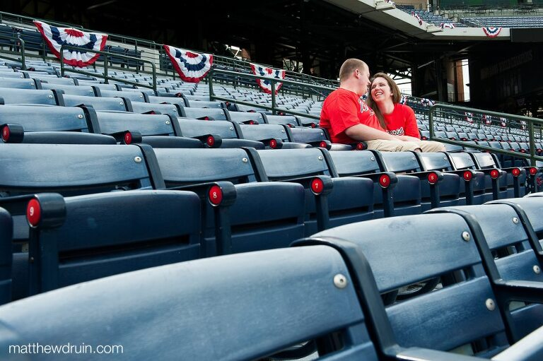 Engaged couple smiling at each other while sitting in baseball stands at Atlanta Braves Turner Field engagement session